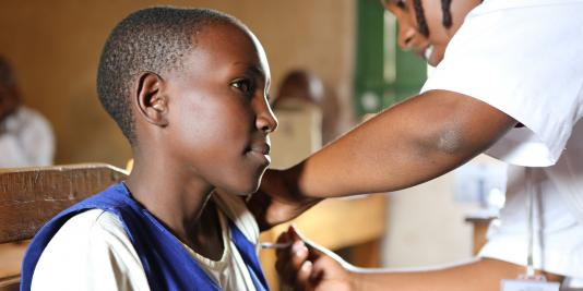 A girl receives the HPV vaccine at her school in the Southern Province of Rwanda. © 2012 Christine McNab/WHO.